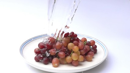 Fototapete - Pour fresh water to a pile of grapes in a white plate in Slow Motion