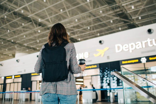 Young girl stands in front of departure area at the airpot with her backpack and coffee cup.  View from the back.
