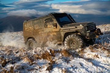 Front view of massive 4x4 off-road car on the dirty snowed ground panorama in mountains.
