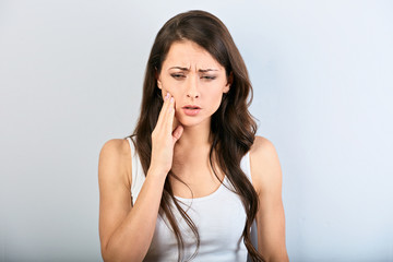 Tooth pain and dentistry. Beautiful young woman suffering from strong teeth pain and the hand touching the cheek. Female in casual clothing feeling painful toothache.