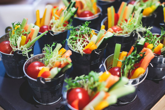 Beautifully decorated catering banquet table with variety of vegetables and different vegan vegetarian snacks on corporate christmas birthday party event or wedding celebration