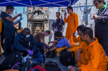 Crew members of the Kokuka Courageous oil tanker receive medical attention from military personnel aboard missile destroyer USS Bainbridge, at sea
