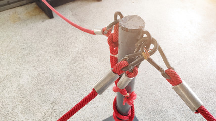 Red rope with metal hooks attached on grey iron pole to form up a barrier fence to control and restrict people to walk in line and prevent access to unauthorized area.