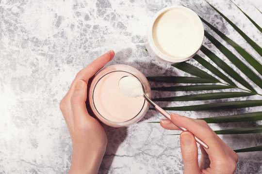 Woman hands, collagen powder and smoothie.