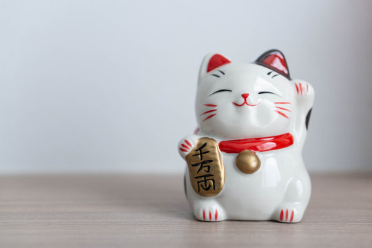 Maneki neko lucky cat show text on hand meaning rich on wood table background, select focus