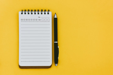 top view of empty open lined notebook and pen on yellow blackground with copy space, flat lay Wall mural