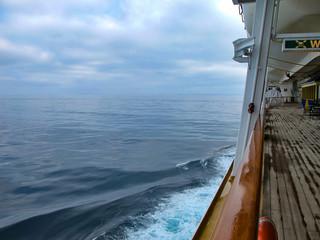 Photo sur Aluminium Pôle Holzplanken auf Bootsdeck von Kreuzfahrtschiff mit Horizont, Meer und Wolken