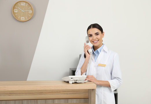 Receptionist talking on telephone at desk in modern clinic