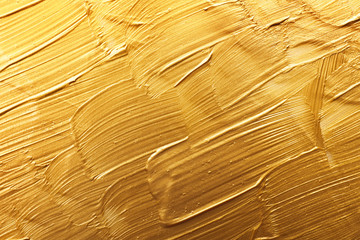 Strokes of gold paint as background, top view