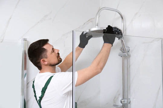 Professional handyman working in shower booth indoors