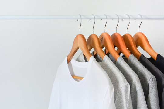 close up collection of black, gray and white color (monochrome) hanging on wooden clothes hanger in closet or clothing rack over white background, copy space