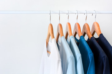 close up collection shade of blue tone color t-shirts hanging on wooden clothes hanger in closet or clothing rack over white background with copy space