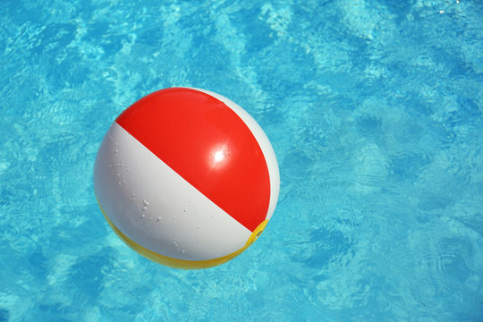 Colorful beach ball floating in swimming pool on sunny day. Space for text