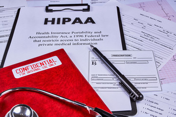 Health Insurance Portability and accountability act HIPAA, red folder with inscription confidential, prescription pen and stethoscope on the medical documents background