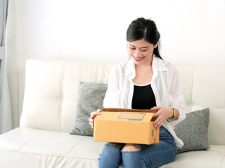 Delivery, mail and people concept - smiling Asian woman opening cardboard box at home.