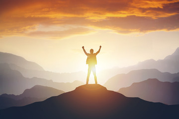 Man standing on edge of mountain feeling victorious with arms up in the air. Wall mural