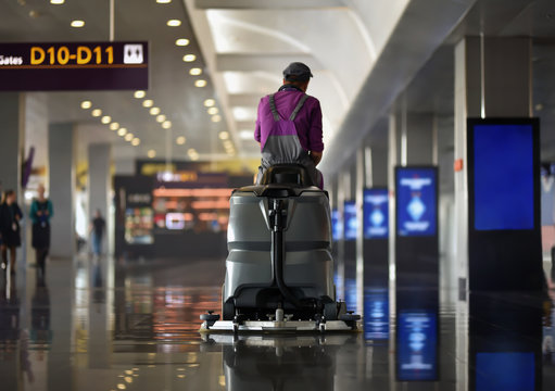 machine of floor scrubber with cleaner man in airport