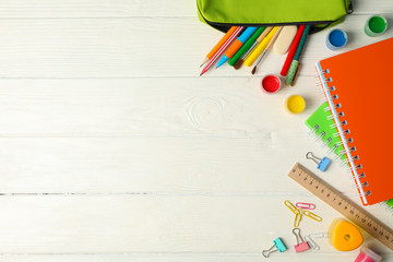 Flat lay composition with school supplies on white wooden background, space for text