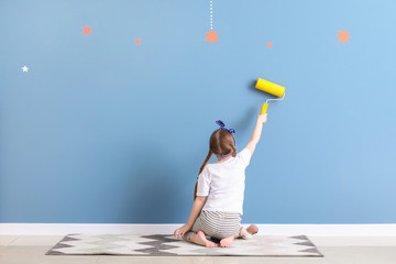 Cute little girl painting wall in room
