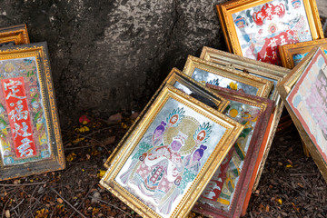 Framed Religious Pictures relating to Buddhism left in the roots of a tree