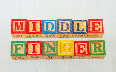 The term middle finger visually displayed on a clear background using colorful wooden blocks image in landscape format