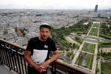 """French street artist Saype poses at the Eiffel Tower in front of his giant artwork """"Beyond Walls"""", a spray-paint series of interlocked hands across the lawns of the Champs de Mars in Paris"""