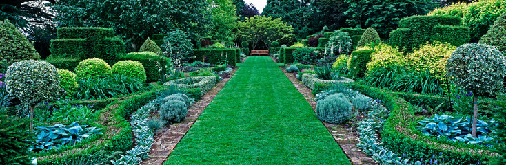 Spoed Foto op Canvas Tuin Panoramic view of the pattern border in the upper gardenof a country house garden