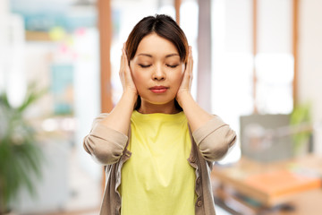 people, emotion and stress concept - asian young woman closing ears by hands over office background