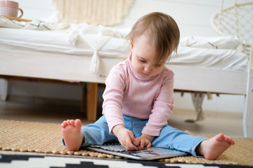 A little two-year-old girl sits on the bedroom floor and plays. Toy calendar in the form of a puzzle. Educational games for children. Bright bedroom, black and white carpet near the bed