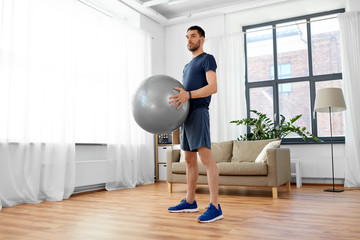 fitness, sport and healthy lifestyle concept - man exercising with ball at home
