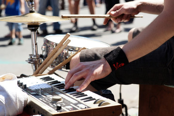 Drummer close-up playing drums and keyboard on the street - open air concert