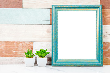 Blank vintage photo frame on wooden wall with cactus plant.