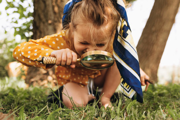 Image of cute kid with magnifying glass exploring the nature outdoors. Adorable little girl playing in the forest with magnifying glass. Curious child looking through magnifier on a sunny day in park