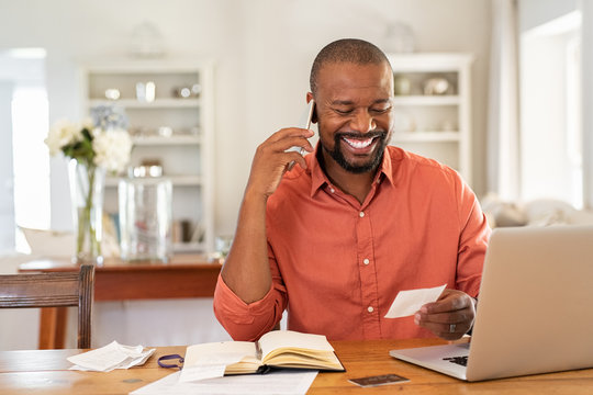 Happy man reading invoice and talking on phone