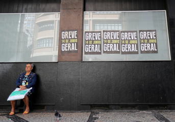 A woman sits in front of a bank during a general strike against the government's pension plan in Rio de Janeiro