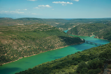 Tagus River and bridge in a valley with hills covered by trees