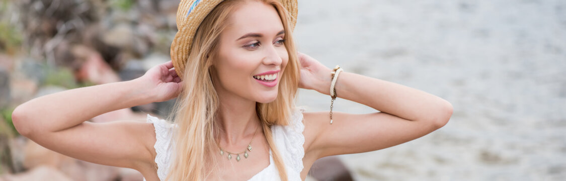 panoramic shot of happy young blonde woman touching straw hat