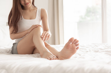 Asian woman applying body lotion on her legs.