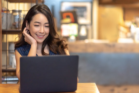 Woman making video call with laptop computer at cafe