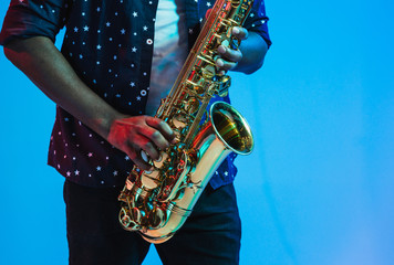 Young african-american jazz musician playing the saxophone on blue studio background in trendy neon light. Concept of music, hobby. Joyful attractive guy improvising. Retro colorful portrait of artist Fotobehang