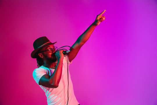Young african-american jazz musician with microphone singing a song on purple studio background in trendy neon light. Concept of music, hobby, inspirness. Colorful portrait of joyful attractive artist