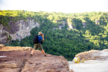Tourists taking pictures of the river East Berbice front of the Kaieteur falls, Guyana. The waterfall is one of the most beautiful and majestic waterfalls in the world with a height of 221 meters. Wor