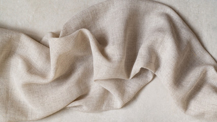 Flap of fine linen or hamp fabric on a gray background