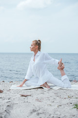 side view of blonde young woman practicing yoga near river
