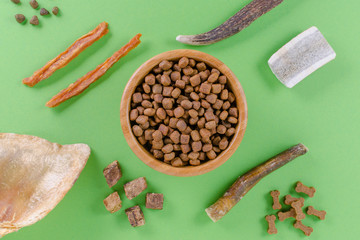 different dog food and snack, chicken filet, antlers, lung, ear on green background