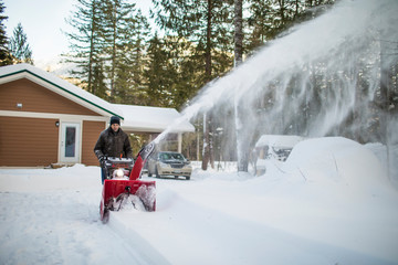 Healthy senior retired man using snow blower machine to clear driveway