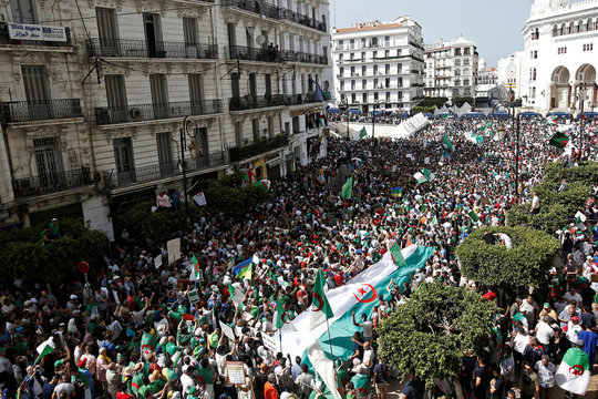 Demonstrators carry banners and flags during a protest demanding the removal of the ruling elite and prosecution of former officials linked to former President Abdelaziz Bouteflika, in Algiers