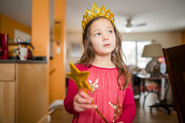 A little girl with a serious expression wears a crown and fairy wand