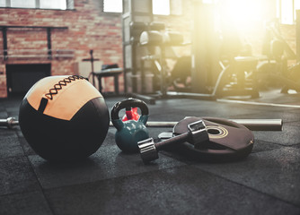 Disassembled barbell, medicine ball, kettlebell, dumbbell lying on floor in gym. Sports equipment for workout with free weight. Functional training Fototapete
