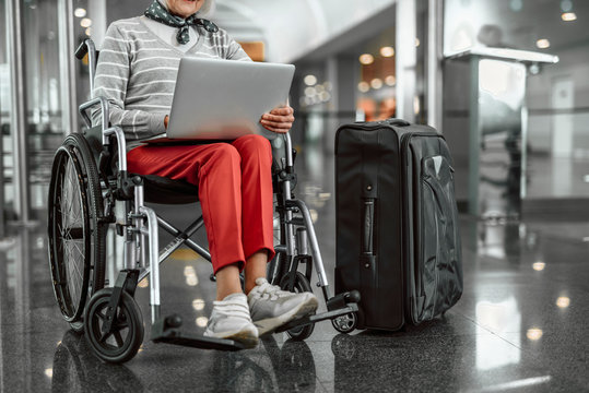 Old lady on disabled carriage working at laptop at airport